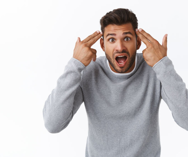 Are you crazy, out your mind. Annoyed and overreacting bothered handsome guy having argument with person making stupid dumb mistake, pointing temples and shouting at friend, quarreling.